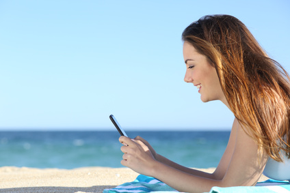 Profile of a woman texting in a smart phone on the beach with the sea in the background